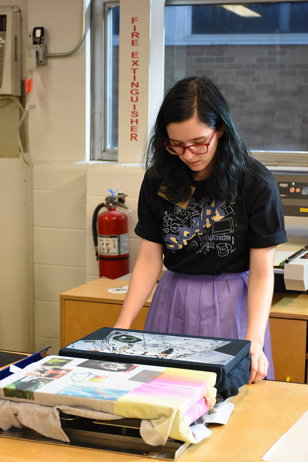 A Spark student employee demonstrates the garment printer