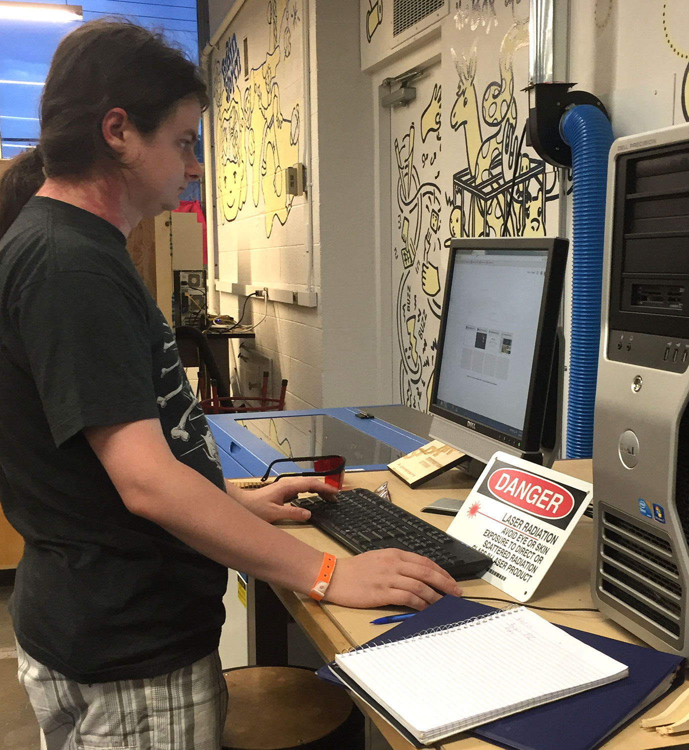 A student works on the laser cutter at Spark