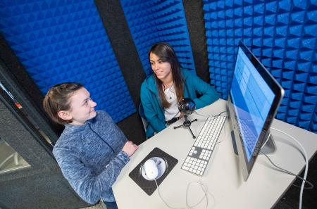 Students record a podcast in the audio recording booth for a course assignment
