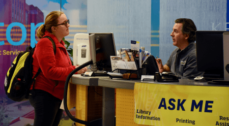 A student works with a librarian at the Ask Me Desk