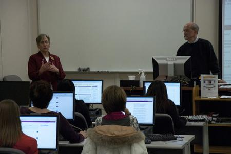 Two lecturers in front of students sitting at computers